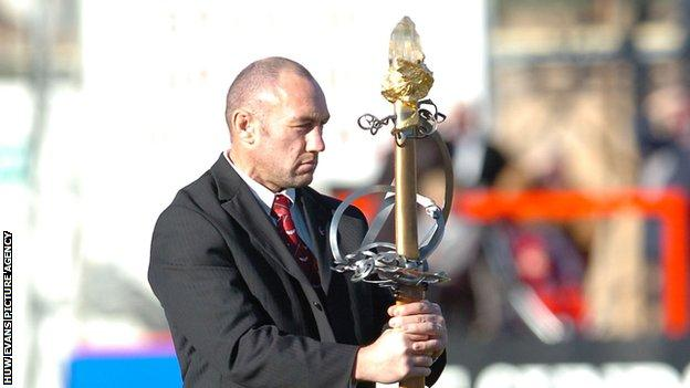 Robin McBryde with the ceremonial sword from the Royal National Eisteddfod of Wales at Ray Gravell's funeral
