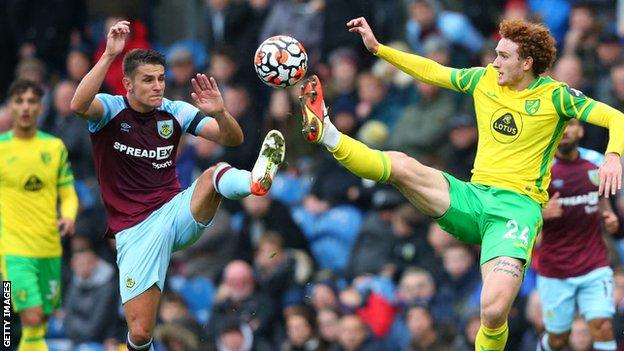 Matthew Lowton of Burnley competes for the ball with Josh Sargent of Norwich City