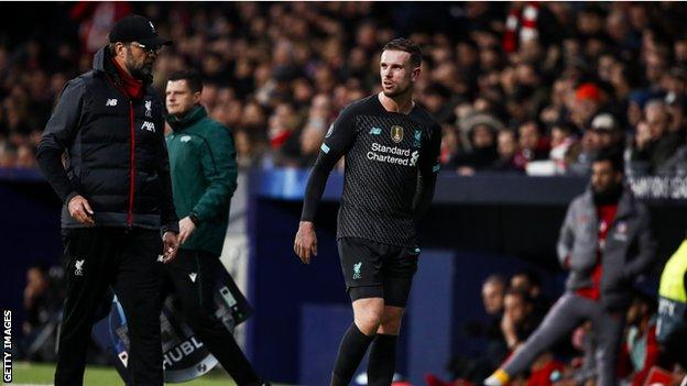 Jordan Henderson feels his hamstring as he walks off the pitch