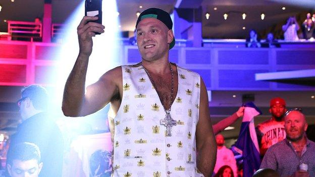 Tyson Fury takes a photo with his phone
