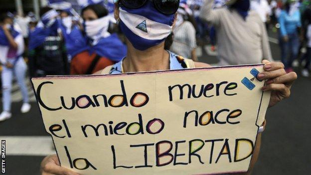 """An anti-government protester holds up a sign which reads """"when fear dies, freedom is born"""" at a rally in Managua, Nicaragua's capital"""