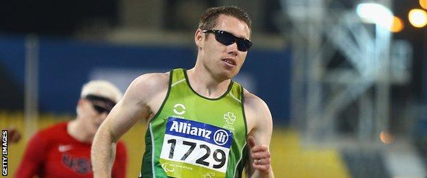 Jason Smyth crosses the line after retaining his T13 100m title in Doha