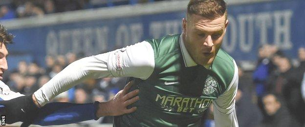 Hibs striker Anthony Stokes holds off a Queen of the South defender