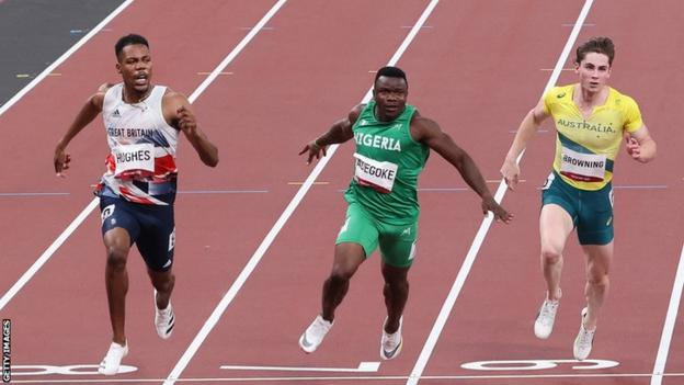 Nigeria's Enoch Adegoke (centre) lunges for the line in his semi-final of the men's 100m at the Tokyo Olympics