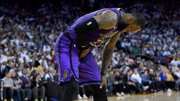 LeBron James bends over in pain after straining his groin against the Golden State Warriors