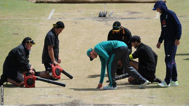 Groundstaff attempt to dry the pitch at Perth as Steve Smith and Joe Root inspect it