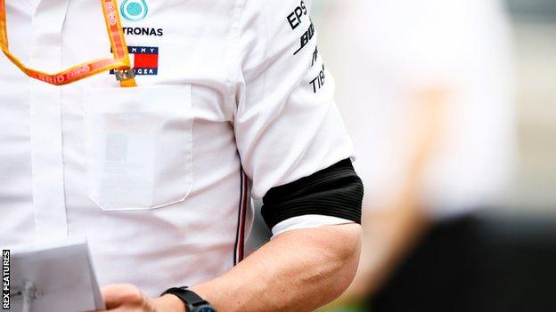 Mercedes team members are wearing black arm bands in tribute