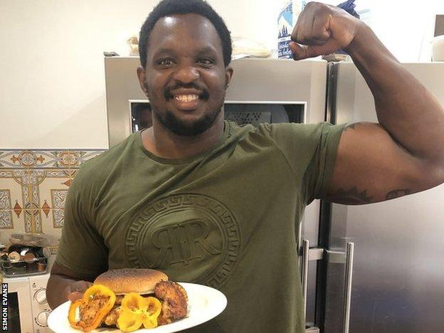 Dillian Whyte poses with the chicken burger he made for the charity chicken burger challenge against Eddie Hearn