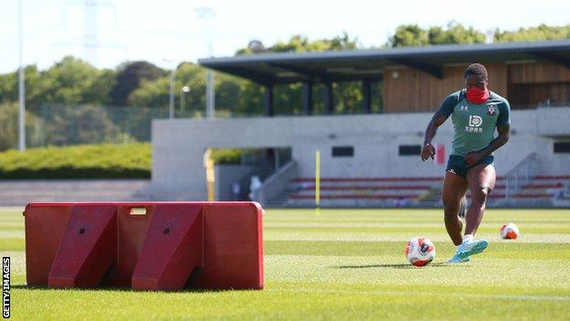 Southampton forward Michael Obafemi wears a cover over his mouth as he takes part in training