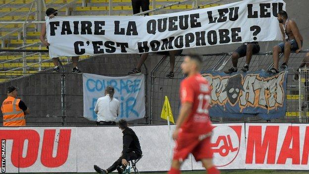 Montpellier's French midfielder Jordan Ferri (C) walks in front of a banner related to homophobia