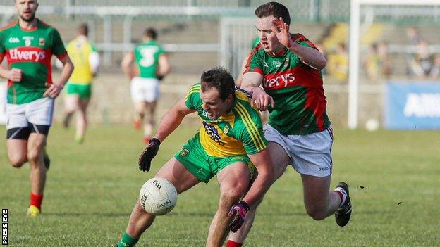 Michael Murphy stoops to win possesion ahead of Mayo's Shane Nally