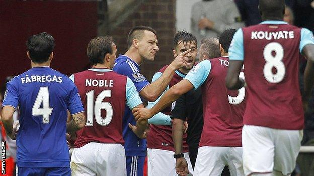 West Ham and Chelsea players surround referee Jon Moss during a game between their sides in October
