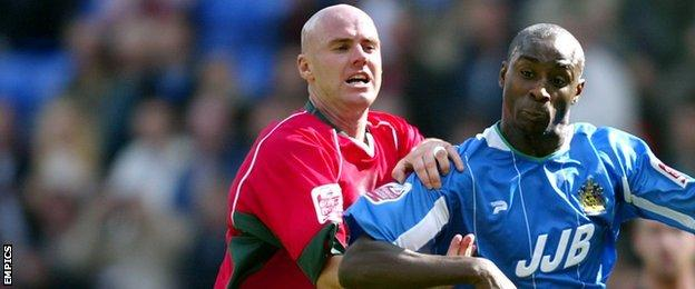 Cardiff City defender Rob Page challenges Wigan Athletic striker Jason Roberts during a Championship fixture at the DW Stadium in August 2004