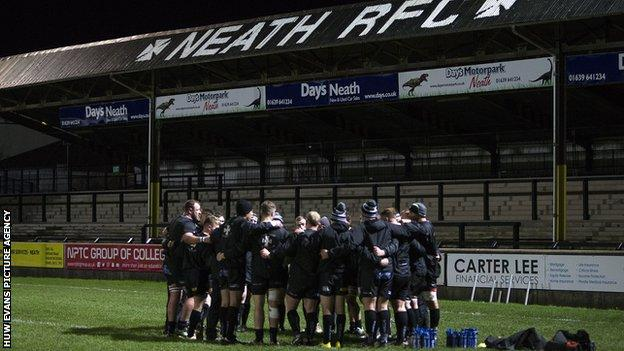 Neath players in huddle below a painted sign on the grandstand at the Gnoll ground