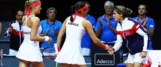 French Fed Cup team captain Amelie Mauresmo (R) encourages Caroline Garcia (C) and Kristina Mladenovic