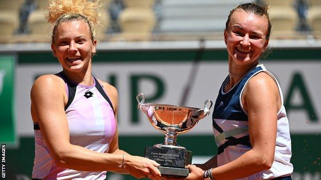 Katerina Siniakova and Barbora Krejcikova jump in the air with their French Open trophy