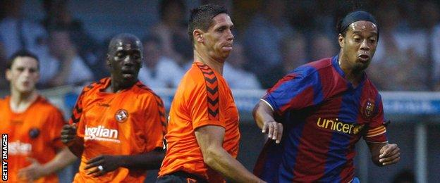 United's Lee Wilkie tackles Barcelona star Ronaldinho during their friendly at Tannadice in July 2007