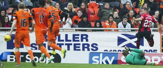 Lewis Vaughan (right) flicks the ball over Dundee United keeper Cammy Bell to score Dumbarton's second goal