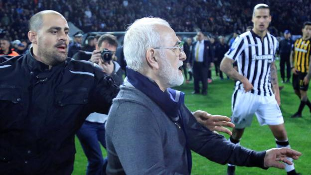 President of Greek club PAOK Salonika apologises after invading pitch with a gun