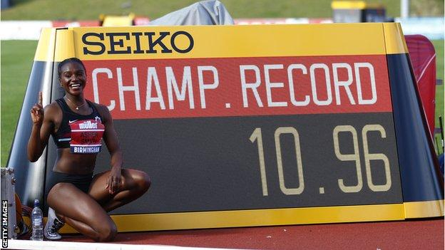 Dina Asher-Smith poses next to the time 10.96