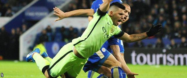 Sergio Aguero is challenged by Gokhan Inler