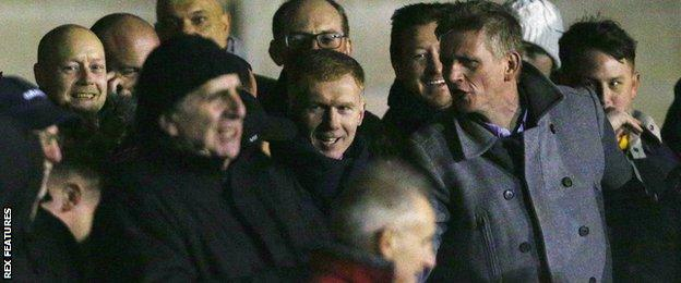 Paul Scholes (centre) watches on from the stands at Moor Lane