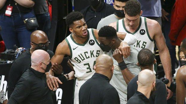 Giannis Antetokounmpo being helped off court
