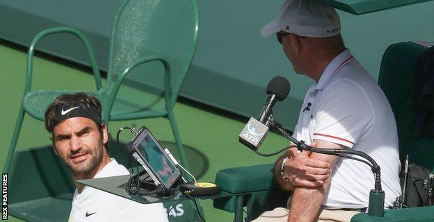 Roger Federer speaks to the umpire