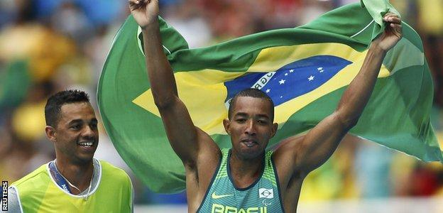 Brazil's Ricardo Costa de Oliveira celebrates with the Brazilian flag after winning gold in the T11 long jump