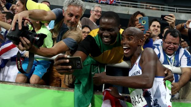 Mo Farah poses for a selfie with a fan after winning the 5,000m.
