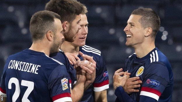 Andrew Considine, Declan Gallagher and Scott McTominay congratulate Lyndon Dykes