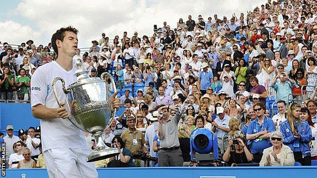 Andy Murray carries the Queen's trophy after winning his first title at the west London club in 2009