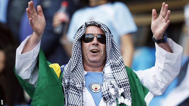 A Manchester City supporter dons a traditional Middle Eastern headdress to celebrate the buyout of the club by the Abu Dhabi United Group