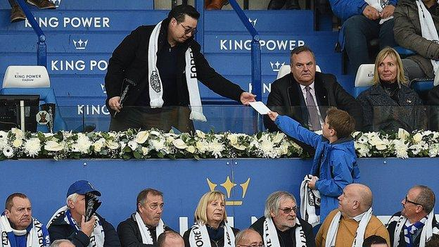 Vichai Srivaddhanaprabha's son Aiyawatt is handed an envelope by a young fan during Leicester's game against Burnley