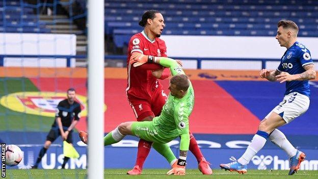 Everton's Jordan Pickford collides with Liverpool's Virgil van Dijk