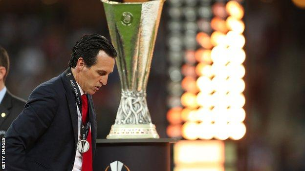Unai Emery walks past the Europa League trophy after Arsenal were beaten by Chelsea in 2019