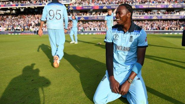 Jofra Archer kneels in celebration after winning the Cricket World Cup with England