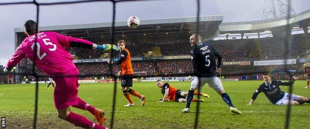 Dundee United's Chris Erskine slides in to score the opener in a 6-2 win over their city rivals on New Year's Day