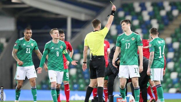 Paddy McNair receives a yellow card for a tackle