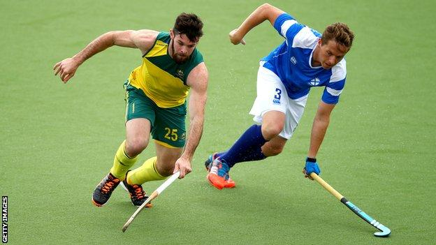 Trent Mitton of Australia is challenged by Scotland's David Forsyth during the Glasgow 2014 men's preliminaries pool match between Australia and Scotland at the Glasgow National Hockey Centre