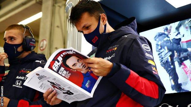 Alex Albon reads a magazine