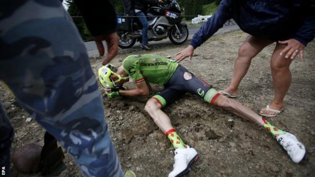 France's Pierre Rolland slips on the wet tarmac