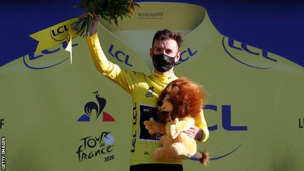 Adam Yates celebrates taking the yellow jersey on the podium