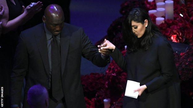 Basketball legend Michael Jordan (left) helps Vanessa Bryant (right) down from the stage after she gives a speech at Kobe and Gianna Bryant's memorial service