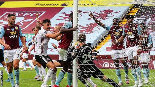 Aston Villa goalkeeper Orjan Nyland holds the ball behind the goalpost