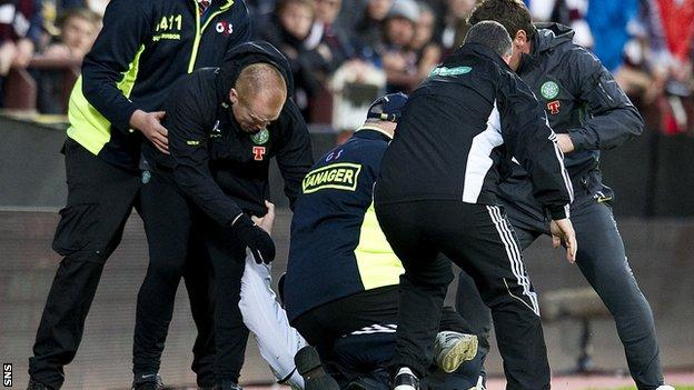 A Hearts fan is restrained after running at Neil Lennon