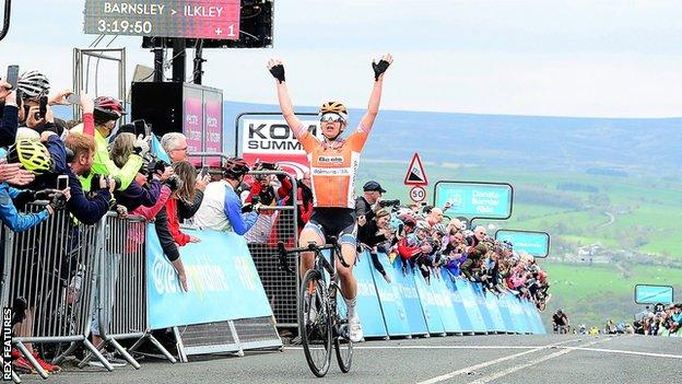 American Megan Guarnier raises her hands in celebration as she crosses the line after winning the 2018 women's Tour de Yorkshire