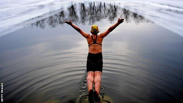Woman diving into a pool cut into a frozen lake
