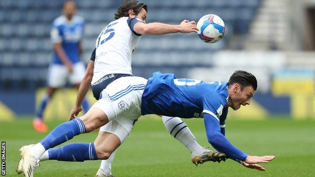 Kieffer Moore tumbles to the ground after a challenge with Preston's Joe Rafferty