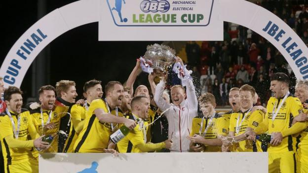 Cliftonville players collect the League Cup in front of their fans at Solitude